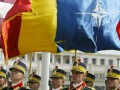 Romanian soldiers form an honour guard beneath Romanian and NATO flags during a NATO flag-raising ceremony in Bucharest, to mark the entr of seven former communist states into the US-led military alliance 02 April 2004. The US-led alliance's expansion takes its military muscle to the Russian border with the entry of Bulgaria, Estonia, Latvia, Lithuania, Romania, Slovakia and Slovenia. AFP PHOTO DANIEL MIHAILESCU